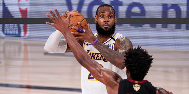 Los Angeles Lakers' LeBron James (23) looks to pass the ball against Miami Heat's Jimmy Butler (22) during the first half in Game 3 of basketball's NBA Finals, Sunday, Oct. 4, 2020, in Lake Buena Vista, Fla. (AP Photo/Mark J. Terrill)