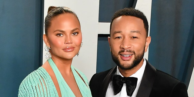 John Legend (reg) and Chrissy Teigen (links) used his music video for the song 'Wild' to allude to the star's pregnancy. (Photo by Allen Berezovsky/Getty Images)