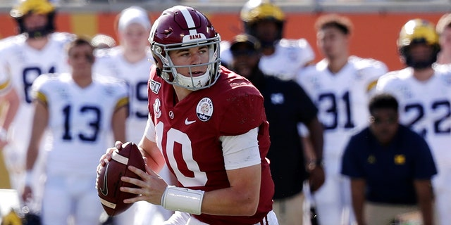 In this Jan. 1, 2020, file photo, Alabama quarterback Mac Jones (10) rolls out as he looks for a receiver during the first half of the Citrus Bowl NCAA college football game against Michigan in Orlando, Florida. (AP Photo/John Raoux, File)