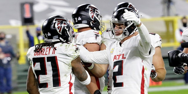 Atlanta Falcons' Todd Gurley (21) celebrates a touchdown run with quarterback Matt Ryan (2) during the second half of an NFL football game against the Green Bay Packers, Monday, Oct. 5, 2020, in Green Bay, Wis. (AP Photo/Mike Roemer)