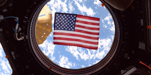 An American flag in one of the windows of the International Space Station's cupola