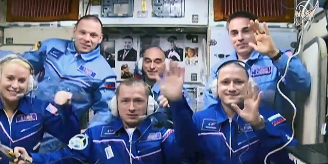 (Front row from left) Expedition 64 crew members Kate Rubins, Sergey Ryzhikov and Sergey Kud-Sverchkov join Expedition 63 crew members (back row from left) Ivan Vagner, Anatoly Ivanishin and Chris Cassidy inside the space station's Zvezda service module. (Front row from left) Expedition 64 crew members Kate Rubins, Sergey Ryzhikov and Sergey Kud-Sverchkov join Expedition 63 crew members (back row from left) Ivan Vagner, Anatoly Ivanishin and Chris Cassidy shortly after the Soyuz capsule's arrival on Oct. 14, 2020.