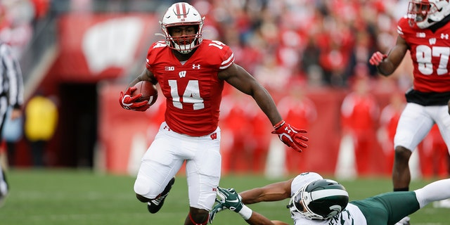 FILE - In this Oct. 12, 2019, file photo, Wisconsin running back Nakia Watson (14) runs past Michigan State safety Xavier Henderson (3) during the first half of an NCAA college football game, in Madison, Wis. (AP Photo/Andy Manis, File)