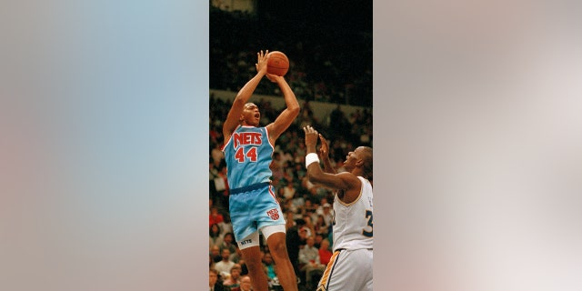 Derrick Coleman of the New Jersey Nets (44) takes a shot over the top of Tyrone Hill of the Golden State Warriors (32) during first quarter action at the Oakland Coliseum, 十一月. 24, 1990. (AP Photo/Alan Greth)