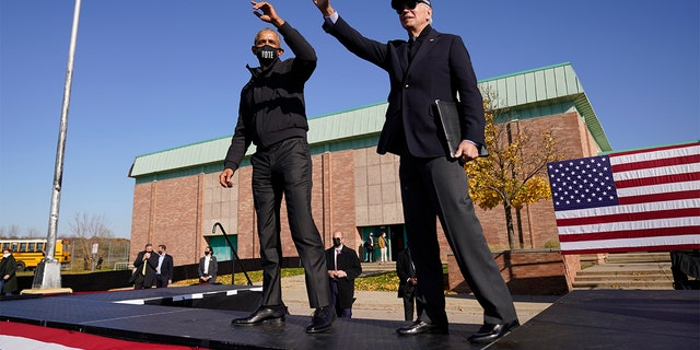 FILE - Biden and Obama wave to the audience at a rally at Northwestern High School in Flint, Mich., sábado, Oct. 31, 2020. (AP Photo/Andrew Harnik)