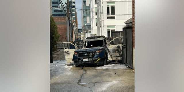 A man allegedly threw a flaming piece of lumber into a Seattle police vehicle Thursday, injuring one officer.