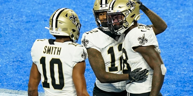 New Orleans Saints running back Latavius Murray, right, is congratulated by teammates wide receivers Marquez Callaway (12) and Tre'Quan Smith (10) after scoring on a 6-yard run during the second half of an NFL football game against the Detroit Lions, Sunday, Oct. 4, 2020, in Detroit. (AP Photo/Carlos Osorio)