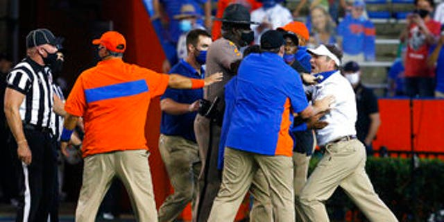 Florida coach Dan Mullen, right, is held back by coaches and law enforcement after a fight broke out at the end of the first half of the team's NCAA college football game against Missouri in Gainesville, Fla., Saturday, Oct. 31, 2020. (Associated Press)