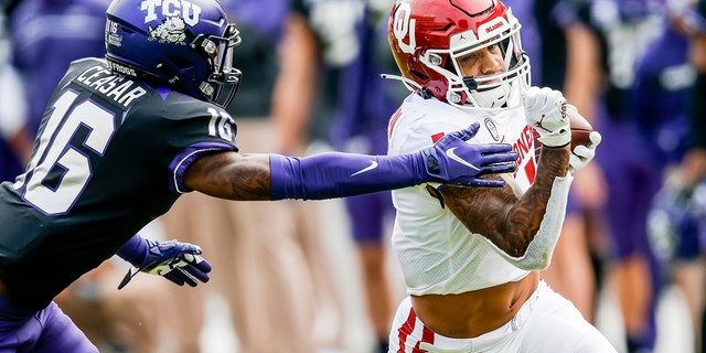 Oklahoma running back Seth McGowan (1) carries the ball as TCU cornerback C.J. Ceasar II (16) defends during the second half of an NCAA college football game, Saturday, Oct. 24, 2020, in Fort Worth, Texas. Oklahoma won 33-14. (AP Photo/Brandon Wade)