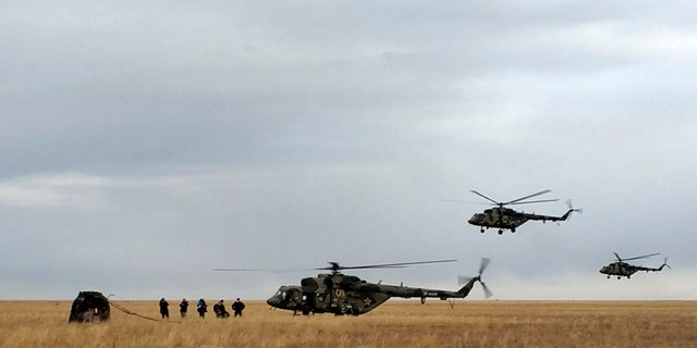 In this photo released by Rosaviatsiya, Russian rescue team helicopters land near a Russian Soyuz MS-16 capsule, left, landed near town of Dzhezkazgan, Kazakhstan, Thursday, Oct. 22, 2020. Rosaviatsiya via AP