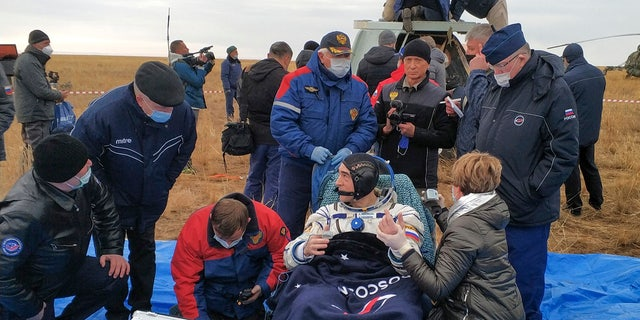 In this photo released by Rosaviatsiya, Roscosmos' cosmonaut Anatoly Ivanishin sits in a chair shortly after the landing near town of Dzhezkazgan, Kazakhstan, Thursday, Oct. 22, 2020.
