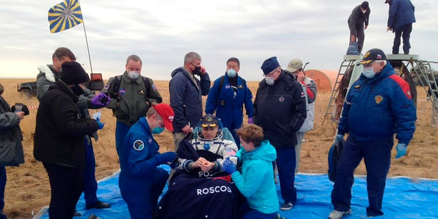 In this photo released by Roscosmos Space Agency, NASA astronaut Chris Cassidy sits in a chair shortly after landing near town of Dzhezkazgan, Kazakhstan, Thursday, Oct. 22, 2020.