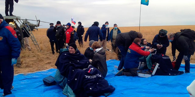 In this photo released by Roscosmos Space Agency, Roscosmos' cosmonauts Anatoly Ivanishin, left, and Ivan Vagner sit in fchairs shortly after the landing near town of Dzhezkazgan, Kazakhstan, Thursday, Oct. 22, 2020.