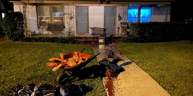 A Texas artist claims his home has become a frequent stop for local police, aftergoing all-out to transform his front yard into a stomach-churning murder scene for Halloween.