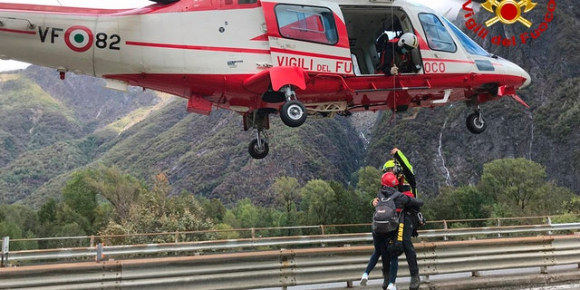 In this image made available Sunday, Oct. 4, 2020, firefighters evacuate people from flooding in the town of Ornavasso, in the northern Italian region of Piedmont. (Firefighter Vigili del Fuoco via AP)