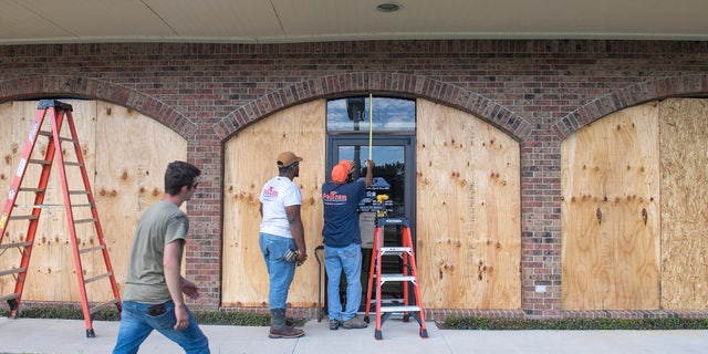 Bernie Arnould, center, gets help from Kaden Ashley and D.J. Hebert, left, all with Pelican Companies, as they board up the windows to the front of MC Bank in Amelia, La., Wednesday, Oct., 7, 2020, in In preparation for Hurricane Delta.