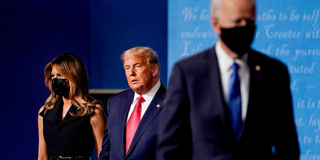 First lady Melania Trump, left, and President Donald Trump, center, remain on stage as Democratic presidential candidate former Vice President Joe Biden, right, walks away at the conclusion of the second and final presidential debate Thursday, Oct. 22, 2020, at Belmont University in Nashville, Tenn. (Associated Press)