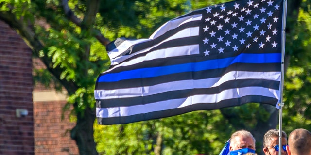 Pro-cop protesters carryng a Blue Lives Matter flag at the protest.