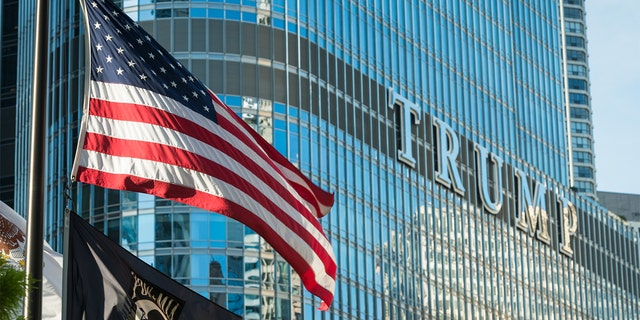 An American flag flying on the Riverwalk at the Vietnam Veterans Fountain late in the day with the Trump Tower.