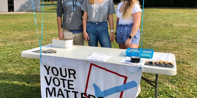 Three students on the campus of the University of Maine work a voter registration table amid the pandemic.