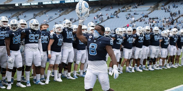 North Carolina's Michael Carter (8) leads the celebration following the Tar Heels' 56-49 victory over Virginia Tech in an NCAA college football game, Saturday, Oct. 10, 2020 at Kenan Stadium in Chapel Hill, N.C. (Robert Willett/The News & Observer via AP)