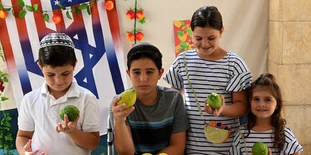 Children celebrate at a Sukka in Israel, holding up citrons.