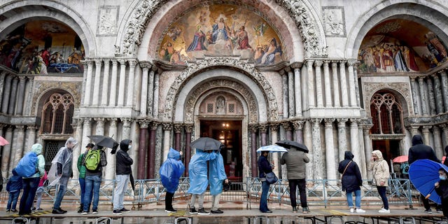 Visitors stand on on a trestle bridges as they admire St. Mark's Basilica during an expected high water, in Venice, northern Italy, Saturday, Oct. 3, 2020.