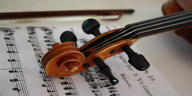 A violin placed over a piece of sheet music.