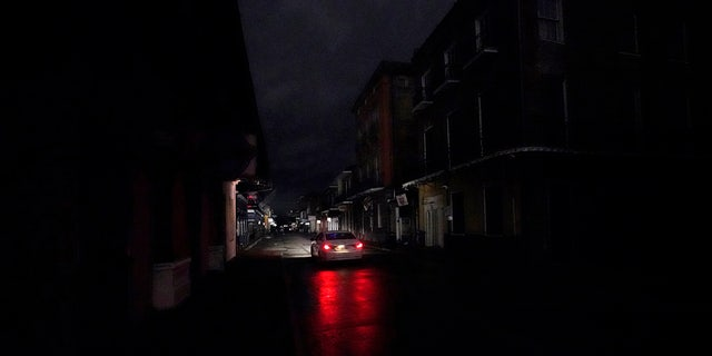 A passing car's headlights illuminate a darkened Bourbon Street in the French Quarter of New Orleans, Woensdag, Okt.. 28, 2020.
