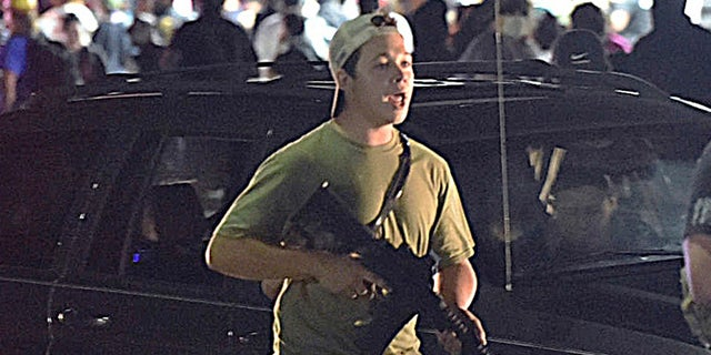 In this Aug. 25, file photo, Kyle Rittenhouse carries a weapon as he walks along Sheridan Road in Kenosha, Wis., during a night of unrest following the weekend police shooting of Jacob Blake. (Adam Rogan/The Journal Times via AP, File)