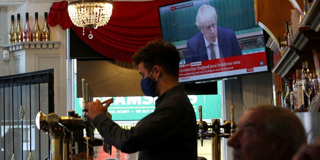 A member of staff pours a drink in the Richmond pub as the TV screen shows Britain's Prime Minister Boris Johnson delivering a statement from the House of Commons, in Liverpool, England, Monday, Oct. 12, 2020. (Peter Byrne/PA via AP)