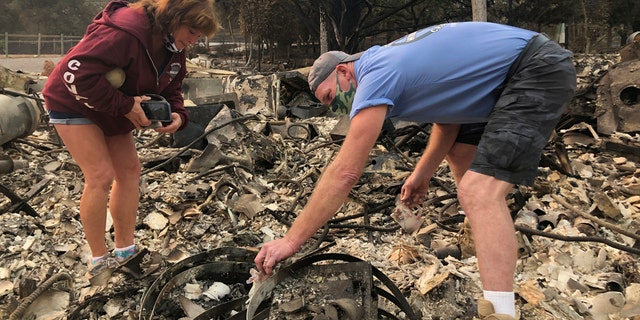 """Kevin Conant and his wife, Nikki, sift through the debris of their burnt home and business """"Conants Wine Barrel Creations,"""" after the Glass/Shady fire completely engulfed it, Wednesday, Sept. 30, 2020, in Santa Rosa, Calif."""