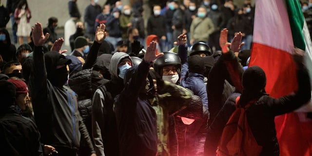 People gathered shout slogans during a protest against the government restriction measures to curb the spread of COVID-19, in Rome  on Tuesday. (Mauro Scrobogna/LaPresse via AP)