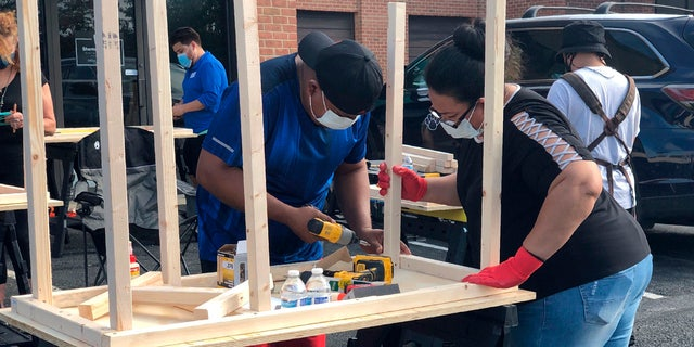 In this photo provided by Jessica Berrellez, volunteers build desks in Gaithersburg, Md. Berrellez and her husband, with the help of some 60 community volunteers, have built and donated over 100 desks to students and families in need.