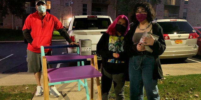 In this photo provided by Jessica Berrellez, her husband, Al Berrellez, left, and daughter Bella Berrellez, right, drop off free desks for Karla Mendez on Tuesday, Sept. 15, 2020, in Gaithersburg, Md.