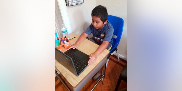 In this photo provided by Jessica Berrellez, student Jordan Dominguez Garcia attends a virtual class using his new desk, which was donated by the community, Thursday, Oct. 8, 2020, in Gaithersburg, Md.