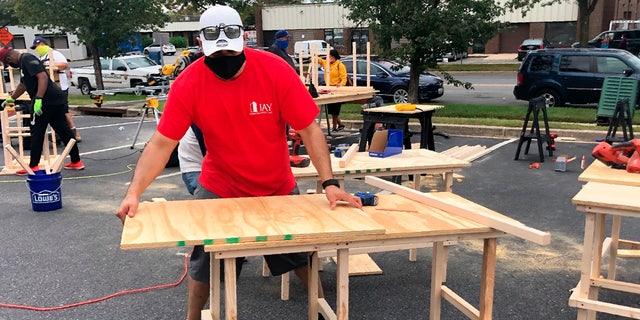 In this photo provided by Jessica Berrellez, her husband, Al Berrellez, builds a desk in Gaithersburg, Md., on Friday, Sept. 25, 2020. (Jessica Berrellez via AP