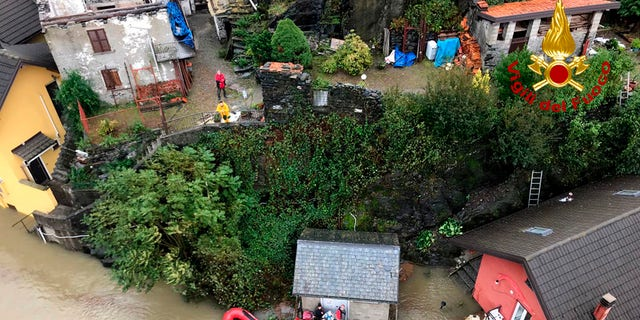 In this image made available Sunday, Oct. 4, 2020, firefighters evacuate people from a house amidst flooding in the town of Ornavasso, in the northern Italian region of Piedmont.