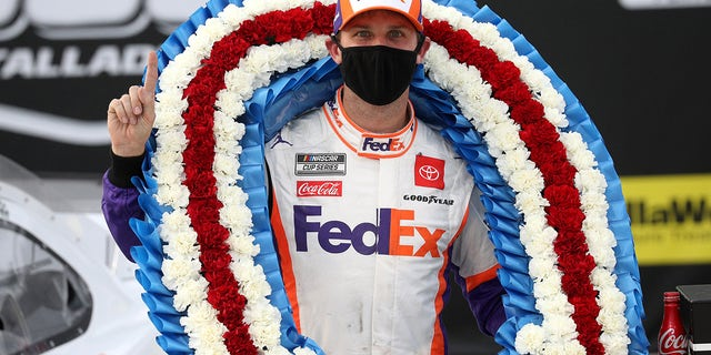 TALLADEGA, ALABAMA - OCTOBER 04: Denny Hamlin, driver of the #11 FedEx Express Toyota, celebrates in Victory Lane after winning the NASCAR Cup Series YellaWood 500 at Talladega Superspeedway on October 04, 2020 in Talladega, Alabama. (Photo by Chris Graythen/Getty Images)