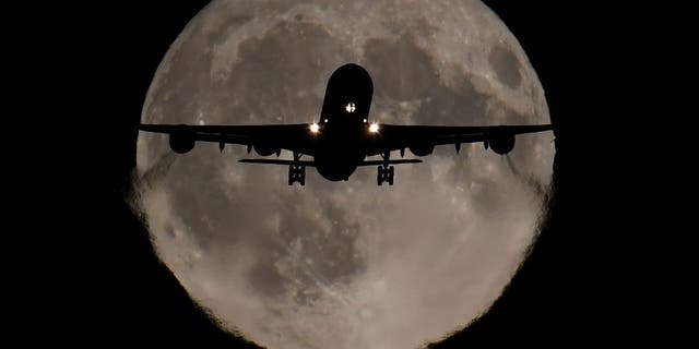 A passenger plane, with a full Harvest moon seen behind, makes its final landing approach towards Heathrow Airport in London. REUTERS/Toby Melville (REUTERS/Toby Melville)