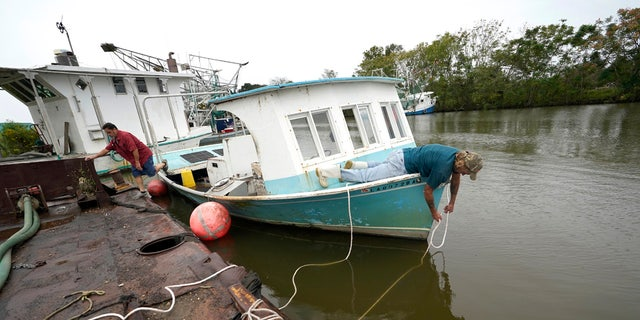 Perry Menesses, right, and Will Guillot secure their boat with more rope after hearing that Hurricane Zeta has increased in strength, in Violet, La., Wednesday, Oct. 28, 2020.