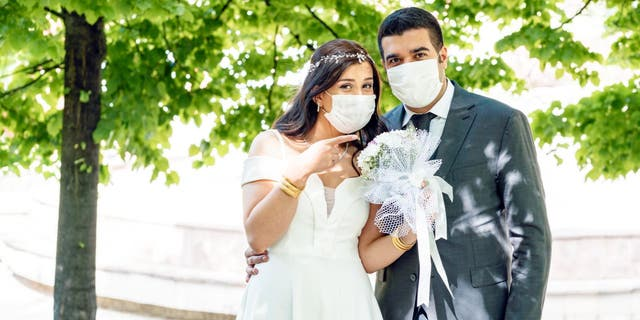 Couples around the globe are adjusting their wedding plans due to the coronavirus pandemic, according to The Knot Worldwide. (iStock)