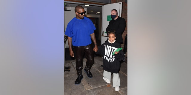 Kanye West with daughter North West in London, England. North, 7, rocks the rapper's 'Vote Kanye' merch.