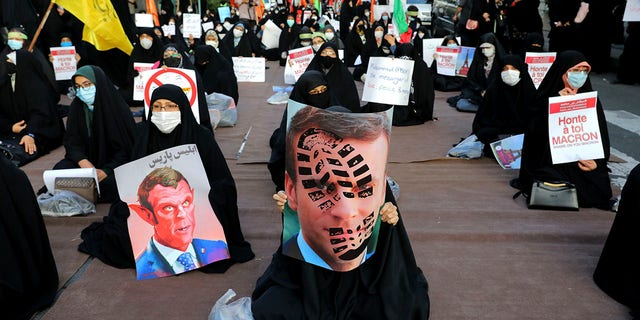 Iranian protesters hold defaced pictures of French President Emmanuel Macron during a protest against Macron and the publishing of caricatures of the Prophet Muhammad they deem blasphemous, in front of French Embassy in Tehran, 伊朗, 星期三, 十月. 28, 2020. (AP Photo/Ebrahim Noroozi)