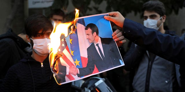 Iranian protesters burn a picture of French President Emmanuel Macron and President Donald Trump during a protest against Macron and the publishing of caricatures of the Prophet Muhammad they deem blasphemous, in front of French Embassy in Tehran, 伊朗, 星期三, 十月. 28, 2020. (AP Photo/Ebrahim Noroozi)