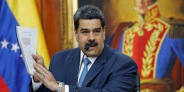 Venezuelan President Nicolas Maduro holds up a copy of his country's case taken to the International Criminal Court regarding U.S. sanctions during a press conference at Miraflores presidential palace in Caracas. A Trump administration official reportedly met with a Maduro ally in September in an attempt to negotiate Maduro's exit from power.
