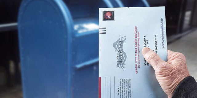 Gualala, CA, July 4, 2020 - Person mailing United States absentee ballot for voting in an election by mail.