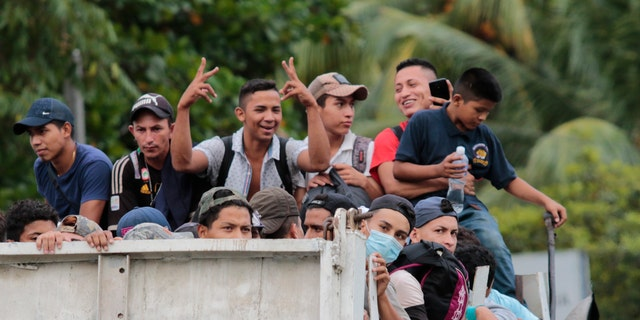 Migrants get a free ride from a trucker toward the Guatemalan border after leaving San Pedro Sula, Honduras. (AP)