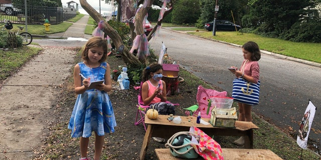 Maya Gebler, center, Cate and Sophie Carroll , right, write letters to fairies in Norfolk, Virginia on Monday Oct. 12, 2020.
