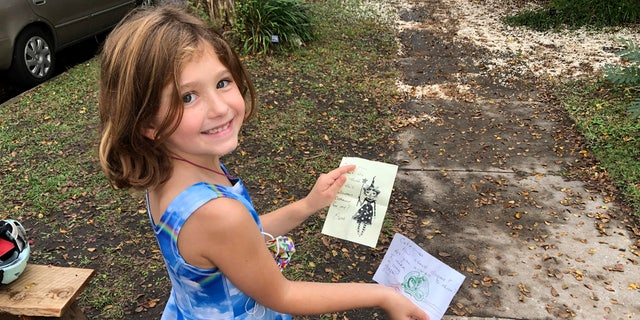 Cate Carroll shows off letters she's received from fairies in Norfolk, Va, on Monday Oct. 12, 2020.